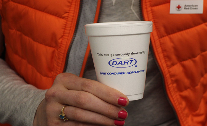 "Person holding white foam cup with the text ""This cup generously donated by Dart Container Corporation"" printed on cup"